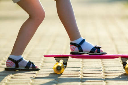 Child slim legs in white socks and black sandals on plastic pink skateboard on bright sunny summer blurred copy space pavement background. Outdoors activities and healthy lifestyle concept. Stockfoto