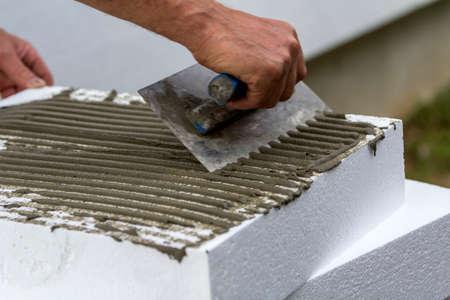 Nahaufnahme der Arbeiterhand mit Kelle, die Kleber auf weiße Polyurethan-Hartschaumplatte für Hausisolierung aufträgt. Moderne Technologie, Renovierung, professionelle Arbeit, Alternative für Mineralwolle-Konzept.
