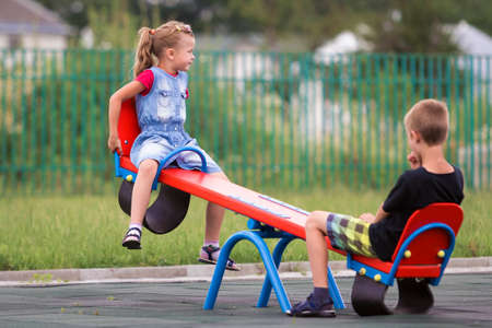 Two young blond children preschooler girl with long ponytail and cute school boy swing on see- saw on bright green blurred background. Joys and games of childhood, outdoors activities concept.
