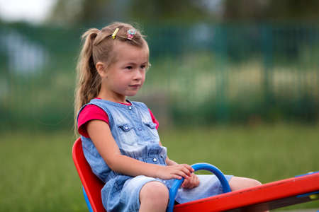 Small cute young blond child girl sits on see- saw swing on warm sunny day on bright green blurred background. Joys and sorrows of childhood, outdoor activity concept.