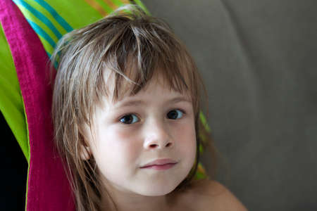 Close-up portrait of young cute pretty preschooler girl with beautiful serious gray eyes and disheveled wet blond hair leaning in lounge on colorful towel on gray copy space background.