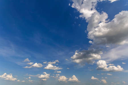 Fantastic panorama view of bright white puffy clouds lit by sun spreading against deep blue summer sky moving with wind. Beauty and power of nature, meteorology and climate changing concept.