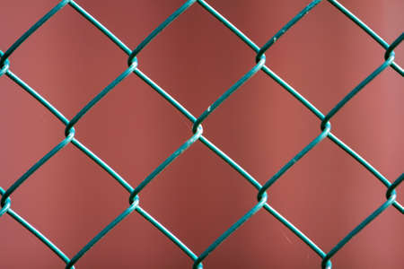 Close-up of isolated painted simple geometric black iron metal wire chain link fence eon dark red background. Fence, protection and enclosure concept. 免版税图像