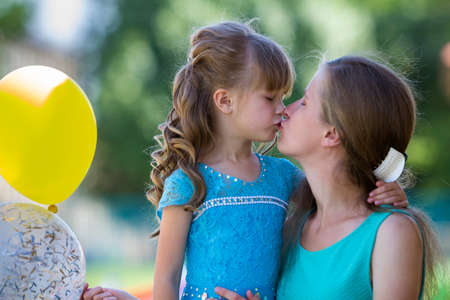 Playful beautiful blond small girl with colorful balloons in nice blue dress kissing her young mother on blurred summer bokeh background. Perfect family relations, happiness, love and care concept.