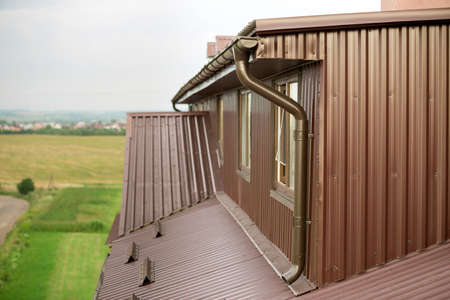 Close-up exterior detail of residential cottage attic room with plastic windows, roof and walls covered with brown metal decorative siding planks, new gutter system on blurred copy space background.