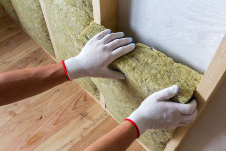 Close-up of worker hands in white gloves insulating rock wool insulation staff in wooden frame for future walls for cold barrier. Comfortable warm home, economy, construction and renovation concept. Stock Photo