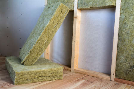 Wooden frame for future walls with drywall plates insulated with rock wool and fiberglass insulation staff for cold barrier. Comfortable warm home, economy, construction and renovation concept.