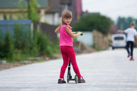 Pretty young long-haired blond child girl in pink clothing with scooter on sunny suburb street and boy on skateboard blurred summer bright background. Children activities, games and fun concept.