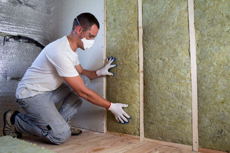 Worker in protective goggles and respirator insulating rock wool insulation in wooden frame for future house walls for cold barrier. Comfortable warm home, economy, construction and renovation concept 스톡 콘텐츠