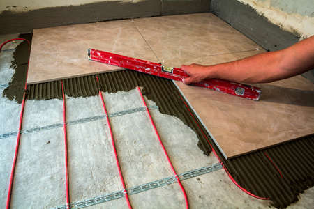 Ceramic tiles and tools for tiler. Worker hand installing floor tiles. Home improvement, renovation - ceramic tile floor adhesive, mortar, level. 写真素材