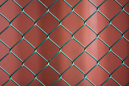 Close-up of isolated painted simple geometric black iron metal wire chain link fence eon dark red background. Fence, protection and enclosure concept. Stok Fotoğraf