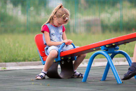 Playground conflicts. Small cute young blond child girl sits moody, angry and offended on see- saw swing on bright green blurred background. Joys and sorrows of childhood, children tantrums concept. Stock Photo