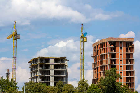 New modern high apartment buildings under construction among green tree tops. Tower crane silhouette on blue summer sky copy space background. Investments and property in ecological area concept.