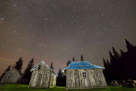 Old wooden weathered unpainted shepherd huts on Carpathian mountains green grassy clearing among pine trees dark silhouettes under beautiful night summer starry sky. Wide angle, copy space background. Stock Photo