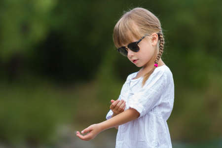 Portrait of cute pretty funny fashionable moody unsatisfied upset angry young girl with blond braids in white dress and dark sunglasses on blurred sunny summer green outdoors copy space background. Reklamní fotografie