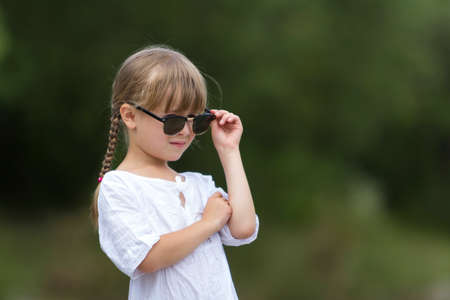 Portrait of cute pretty funny cool fashionable moody unsatisfied angry young girl with blond braids in white dress and dark sunglasses on blurred summer light green outdoors copy space background.