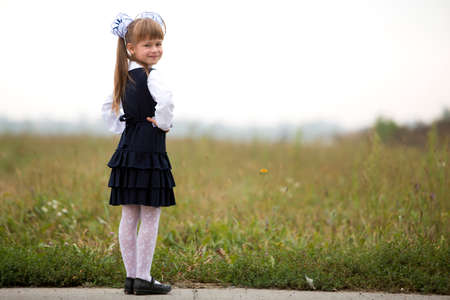 Full-length portrait of cute adorable serious thoughtful first grader girl in school uniform and white bows in long blond hair on blurred light green sunny grass and white sky copy space background.