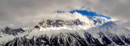 Breathtaking aerial view of Mont Blanc mountain peak covered with shiny snow, ice and glaciers under blue sky with puffy white clouds on the French side of Alps on a clear cold sunny winter day Stock Photo