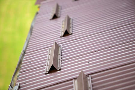 Close-up detail of metal brown shingle tiling house roof surface with rain gutter pipe and snow guards protective fence. Professional work, safety, construction, renovation and durability concept.