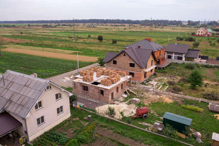 Aerial view of rural land for development in green field. New not finished brick houses and building sites on background of distant city and trees on horizon. Construction and real property concept.