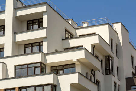 Close-up detail of new white apartment buildings with terraced balconies, shiny windows and low protective fence on flat roof top on blue sky background. Modern architecture, professional building.