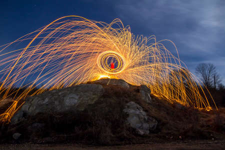 Long exposure shot of man standing on rocky hill spinning steel wool in circle making firework showers of bright yellow glowing sparkles on blue night sky background. Light painting art concept. Redakční