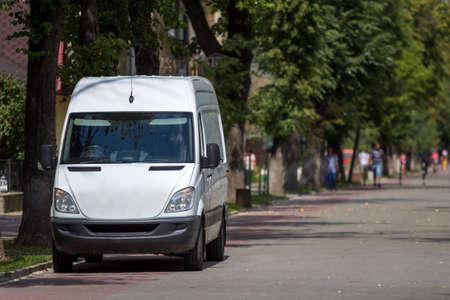 Camioneta minibús de lujo alemán comercial de tamaño mediano de pasajeros blancos estacionados en las calles de la ciudad con siluetas borrosas de peatones y automóviles en movimiento bajo árboles verdes.