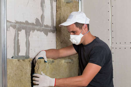 Worker in protective respirator mask insulating rock wool insulation in wooden frame for future house walls for cold barrier. Comfortable warm home, economy, construction and renovation concept