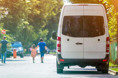 Vista posteriore del furgone minibus di lusso commerciale di medie dimensioni passeggeri bianco parcheggiato n ombra di albero verde sulla strada della città di estate i con sagome sfocate di pedoni e automobili sotto gli alberi verdi.