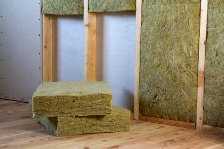 Holzrahmen für zukünftige Wände mit Trockenbauplatten, die mit Steinwolle isoliert sind, und Isolierpersonal für die Kältesperre. Komfortables warmes Haus, Wirtschaftlichkeit, Bau- und Renovierungskonzept.