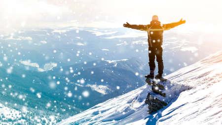 Silhouet van alleen toerist die op de besneeuwde bergtop staat in winnaar pose met opgeheven handen genietend van uitzicht en prestatie op heldere zonnige winterdag. Avontuur, buitenactiviteiten, gezonde levensstijl. Stockfoto