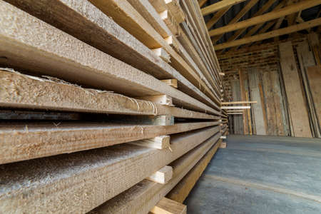 Close-up of neatly piled stack of natural brown uneven rough wooden boards inside attic room under construction. Industrial timber for carpentry, building, lumber material for construction.