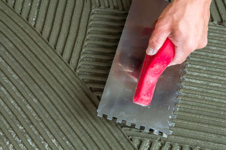 Close-up detail of floor tiles installation. Home improvement, renovation. Workers hand with notched float for tile. Ceramic tile floor adhesive, mortar.