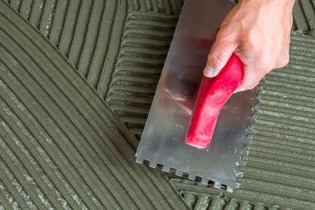 Close-up detail van de installatie van vloertegels. Verbetering van het huis, renovatie. Werknemershand met ingekeepte vlotter voor tegel. Keramische tegelvloerlijm, mortel. Stockfoto