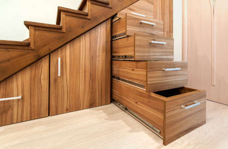 Modern architecture interior with  luxury hallway with glossy wooden stairs in modern storey house. Custom built pullout cabinets on glides in slots under stairs Stock Photo