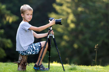 Young blond child boy sitting on tree stump on grassy clearing taking picture with tripod camera.