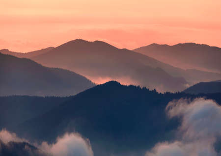 Wide panorama, fantastic view of covered with morning mist green Carpathian mountains at sunset on bright clear orange sky copy space background. Beauty of nature, tourism and traveling concept.
