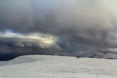 Snow covered Carpathian mountain hills with far away hikers tourists in winter