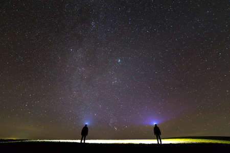 Back view of two men with head flashlights on green grassy field under beautiful dark blue summer starry sky. Night photography, beauty of nature concept. Wide angle shot, copy space background.