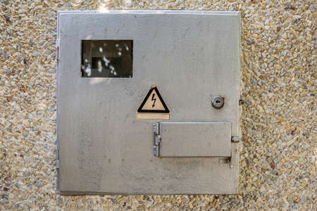 Close-up of locked electrical metal light blue meter box with warning caution sign outside on exterior house wall. Measurement tool and energy saving concept. 免版税图像
