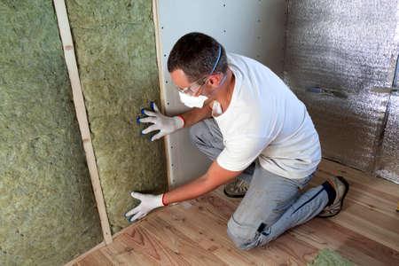 Arbeiter in Schutzbrille und Atemschutzmaske, die Steinwolle-Isolierung in Holzrahmen für zukünftige Hauswände für Kältebarriere isoliert. Komfortables warmes Haus, Wirtschaftlichkeit, Bau- und Renovierungskonzept