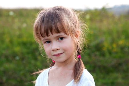 Close-up portrait of cute pretty child girl with gray eyes and long fair hair braids smiling shyly on blurred sunny summer green bokeh background. Beauty, dreams and innocence of childhood.