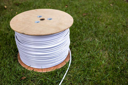 Top view of roll of white industrial electrical cable on large wooden reel isolated outdoors on green grass. Professional construction site cable, reliable wiring and durability. 写真素材 - 114017131