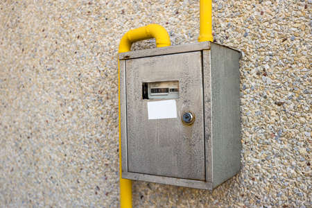 Close-up of metal steel gas meter box with connecting yellow pipes hanging on exterior light stone house wall. Construction, renovation, measurement tool and energy saving concept. Reklamní fotografie