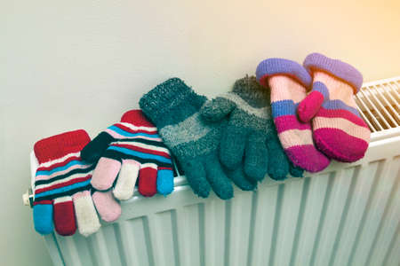 Children's warm hand knitted striped woolen gloves drying on heating radiator after winter day outside