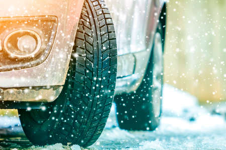 Close-up of car wheel in winter tire on snowy road Stockfoto