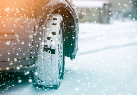 Close up detail car wheel with new black rubber tire protector on winter snow covered road. Transportation and safety concept.
