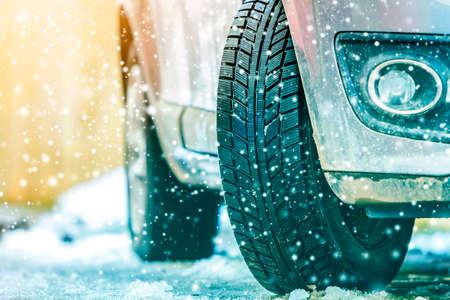 Close-up van autowiel in winterband op besneeuwde weg