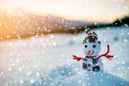 Small funny toy baby snowman in knitted hat and scarf in deep snow outdoor on blurred mountains landscape and falling big snowflakes background. Happy New Year and Merry Christmas greeting card theme. 版權商用圖片