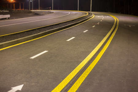 Wide modern smooth empty asphalt highway sharp turn sharp with bright white and double yellow marking sign line. Speed, safety, comfortable journey and professional road building concept.